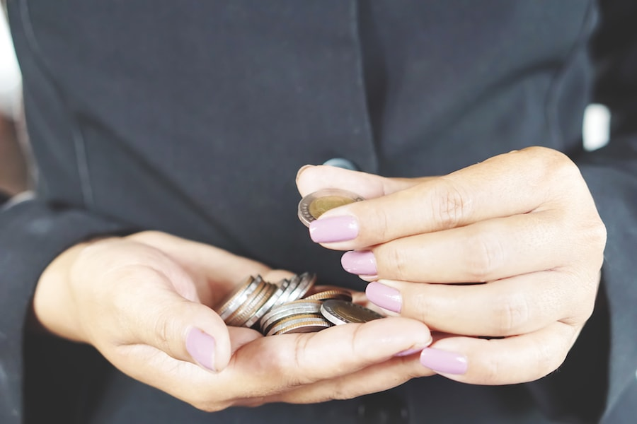 Close up of female hands holding coins saving money in Cedar Park, TX.