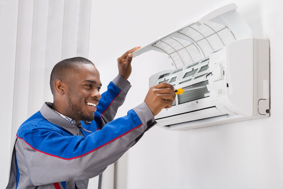 Happy Young African Male Technician Repairing Air Conditioner.