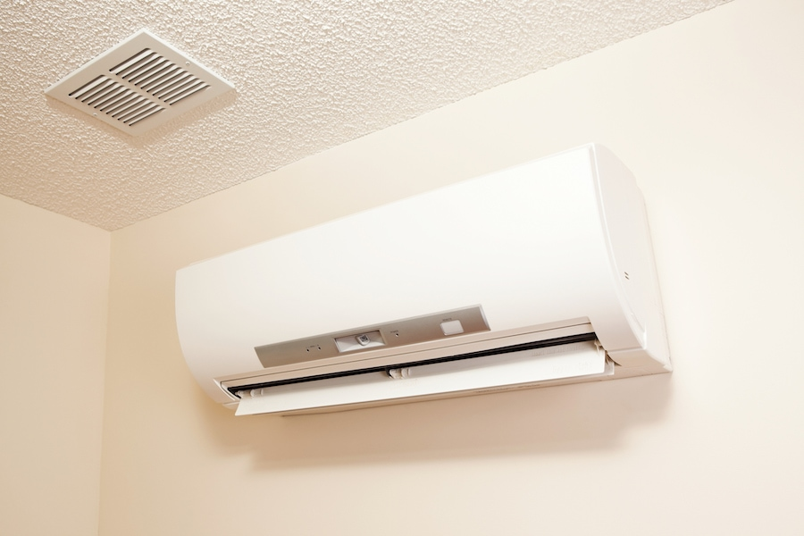 A wall-mount mini-split heating and air conditioning unit installed in a new house. A modern heat pump, this unit heats a house in winter and cools in the summer. This type of system eliminates ductwork which is a primary source of inefficiency in a conventional system making this about 30% more efficient. This particular unit has an eye sensor which pans the room looking for hot or cold spots and directs the airflow accordingly.
