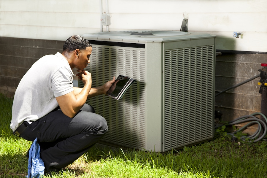 HVAC technician inspecting an air conditioner outside in Austin, TX.
