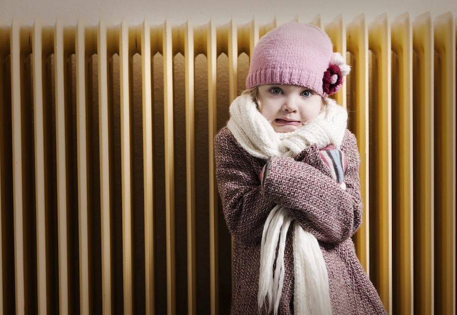 Girl in winter clothes is shivering in front of radiator. Fearful expression. Concept for energy crisis or old heating system.