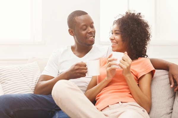 Happy african-american couple drinking coffee at cozy home. Family leisure and relaxation concept, copy space.