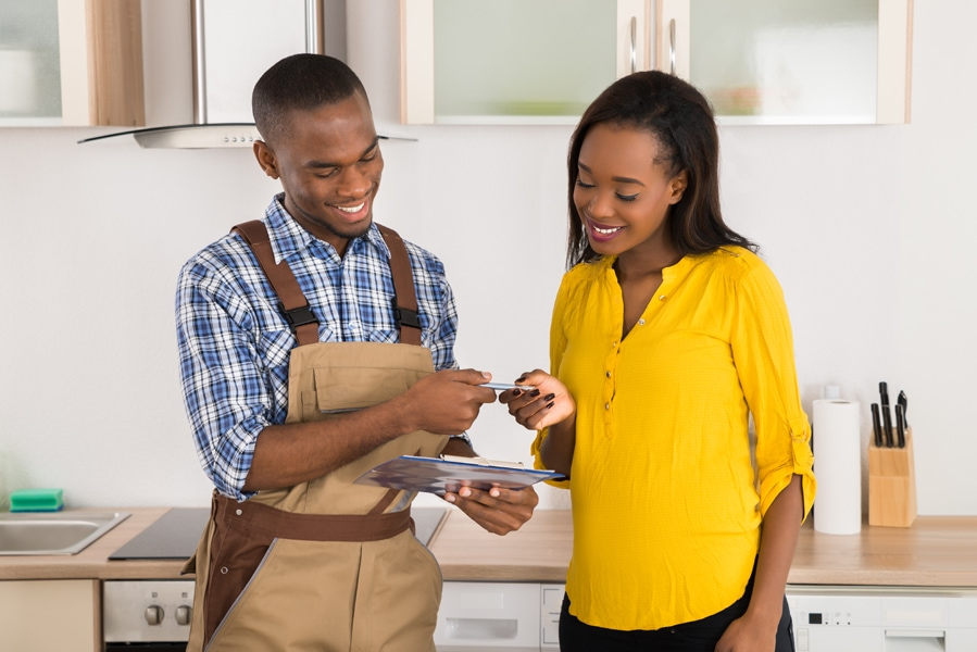 Young Happy Woman And Serviceman Standing In Kitchen With Clipboard.