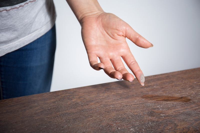 Close-up of dust on woman finger taken from wooden table in Austin, TX